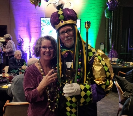 A woman and man dressed up in festive clothing for the EMBA Mardi Gras Banquet