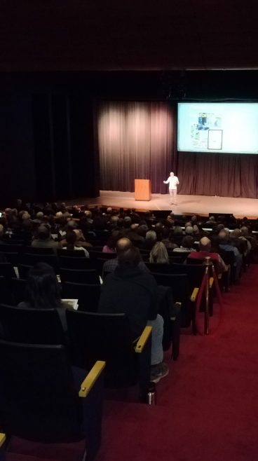 Darkened auditorium with stage highlighted and speaker on stage running slide presentation