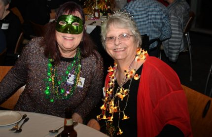Two women dressed up in Mardi Gras attire at the EMBA Mardi Gras Banquet