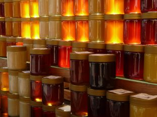 Jarred honey in various colors of red, brown, golden, orange, yellow and more