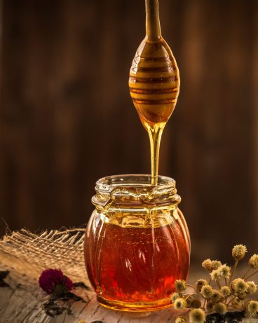 A decorative jar of honey with wooden honey dipper lifted to show honey drizzle