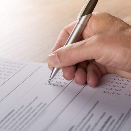 Close up of hand holding a pen filling our a survey