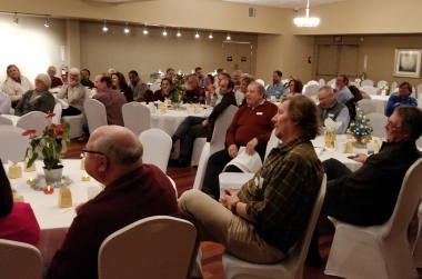 EMBA members seated around tables at the annual EMBA holiday party