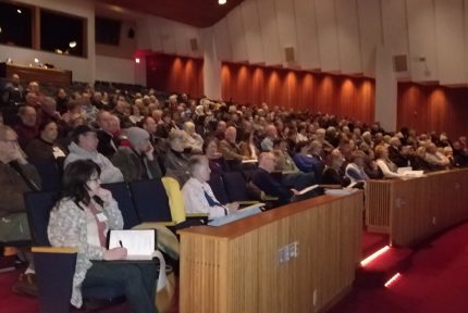 People sitting in an auditorium at an EMBA conference
