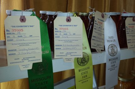 Jars of honey with first, second and third ribbons attached to them from a competition at the Missouri State Fair
