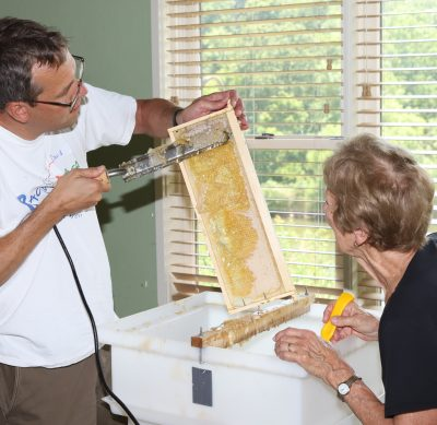 Man using a hot knife to remove cappings that bees put over the honey once it is ready for storage. He is working over a large white tub uncapping station that has a piece of wood across it to hold the frame up while he removes the cappings wax. Lady on the right is watching him to learn how to uncap the honey frames.